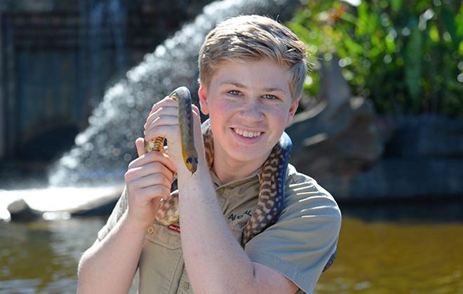 Robert Irwin holding a snake.