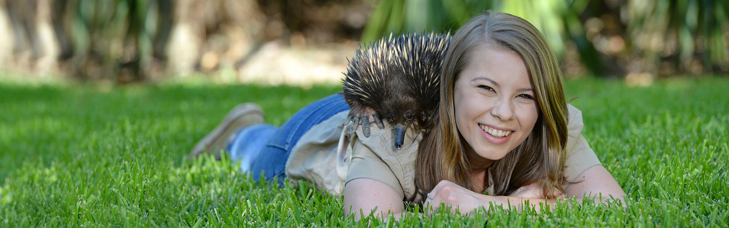 Bindi with an Echidna on her back laying down.