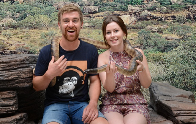 Two visitors with a snake around their neck.